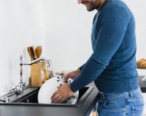 Imagem de um homem lavando louça. Ele segura um prato branco sobre o qual cai água da torneira. O homem veste calças jeans e uma blusa azul-marinho. A parede ao fundo é branca.
