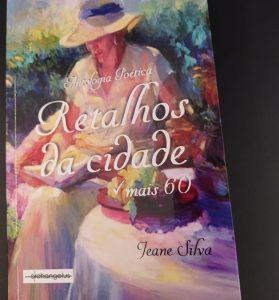 """Capa do livro """"Retalhos da Cidade - Mais 60"""", organizado por Jeane Silva. A imagem é composta por uma arte, em estilo impressionista, de uma mulher sentada lendo um livro e com uma mesa à sua direita sobre a qual estão flores e frutas."""