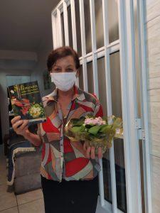 Imagem de Maria Lúcia de Oliveira após o Sarau na Porta. Ela está em frente à casa dela, segurando um vaso pequeno com flores e um livro. Ela está com calça preta, camisa colorida e usa máscara branca.