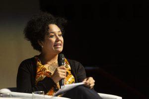 Imagem de Bianca Santana falando em um evento organizado antes da pandemia de Covid-19. Ela segura um microfone com a mão direita e com a mão esquerda segura folhas apoiadas também em uma perna. Ela usa uma blusa preta e uma camiseta amarela com estampas pretas e brancas. O fundo tem pouca iluminação.
